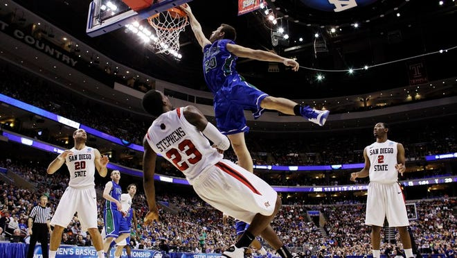 From March 24, 2013, Florida Gulf Coast's Chase Fieler, top, dunks over San Diego State's Deshawn Stephens during the first half of a third-round game of the NCAA college basketball tournament in Philadelphia. The Dunk City Effect, as it's called, accounted for a 35 percent increase in freshman applications following the NCAA run, boosted enrollment from about 13,000 to  more than 15,000, and the academic reputation has been enhanced with higher caliber students being admitted.