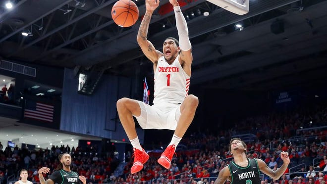 From Dec. 17, 2019, Dayton's Obi Toppin (1) dunks as North Texas' Javion Hamlet (3) looks on during the second half of an NCAA college basketball game, in Dayton, Ohio. Toppin was voted the AP men's college basketball player of the year, Tuesday, March 24, 2020.