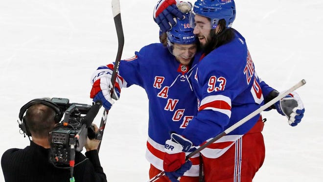New York Rangers left wing Artemi Panarin and center Mika Zibanejad (93) celebrate after Zibanejad scored in overtime of the team's NHL hockey game against the Washington Capitals, Thursday, March 5, 2020, in New York. The Rangers defeated the Capitals 6-5 in overtime; Zibanejad scored five goals.