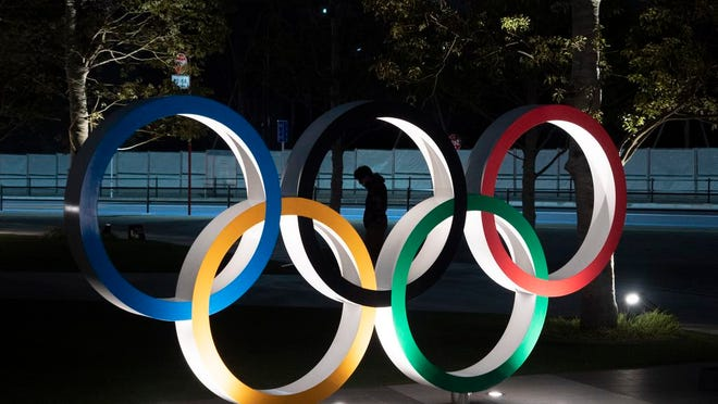"A man is seen through the Olympic rings in front of the New National Stadium in Tokyo, Tuesday, March 24, 2020. IOC President Thomas Bach has agreed ""100%"" to a proposal of postponing the Tokyo Olympics for about one year until 2021 because of the coronavirus outbreak, Japanese Prime Minister Shinzo Abe said Tuesday."