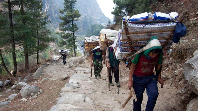 From March 24, 2015, porters with supplies for trekkers head towards Namche, in Zamphute, a village in Nepal. The closure of Mount Everest will have significant financial ramifications for the local Sherpas, cooks, porters and other personnel who make their living during the short climbing window.
