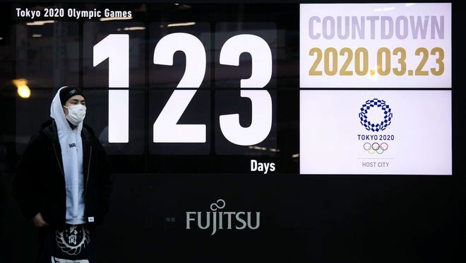 A man stands in front of a countdown display for the Tokyo 2020 Olympics and Paralympics in Tokyo, Monday, March 23, 2020. Japanese Prime Minister Shinzo Abe acknowledged that a postponement of the crown jewel of the sporting world could be unavoidable. Canada and Australia then added to the immense pressure that has been steadily mounting on organizers by suggesting that they wouldn't send athletes to Tokyo this summer.