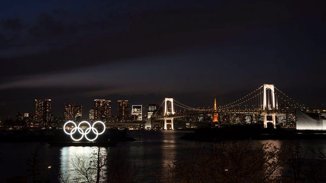 The Olympic rings float in the water near the Rainbow Bridge in the Odaiba section of Tokyo, Monday, March 23, 2020. The Tokyo Olympics are going to happen — but almost surely in 2021 rather than in four months as planned.