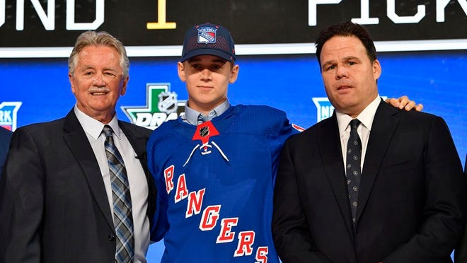 Nils Lundkvist poses for a photo with team representatives after being selected as the number twenty-eight overall pick to the New York Rangers in the first round of the 2018 NHL Draft at American Airlines Center.