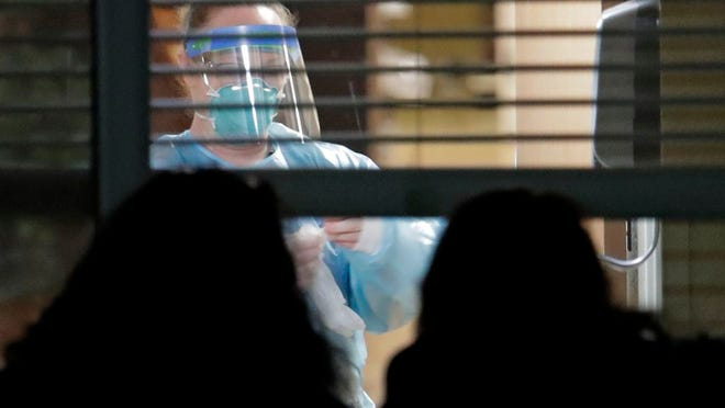 In this March 10, 2020, file photo, a worker wearing protective gear is seen through a window as she works in a room of a woman who has tested positive for the new coronavirus, as her daughters look in from outside the window, at the Life Care Center in Kirkland, Wash., near Seattle. Burgeoning coronavirus outbreaks at this and other nursing homes in Illinois, New Jersey and elsewhere are laying bare the risks of the industry's long-running problems, including a struggle to control infections and a staffing crisis that relies on poorly paid aides who can't afford to stay home sick.