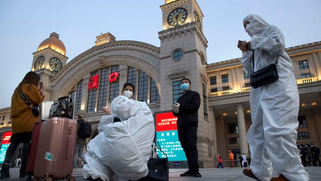 Passengers wearing protective suits to protect against the spread of new coronavirus gather outside of Hankou train station ahead of the resumption of train services in Wuhan in central China's Hubei Province, Wednesday, April 8, 2020. After 11 weeks of lockdown, the first train departed Wednesday morning from a re-opened Wuhan, the origin point for the coronavirus pandemic, as residents once again were allowed to travel in and out of the sprawling central Chinese city.