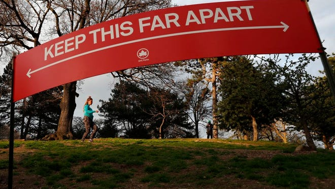 A woman jogs in Brooklyn's Fort Greeene park, Sunday, April 5, 2020, beneath a sign demonstrating the distance people should keep from each other during the coronavirus outbreak in New York. People have been urged to cover their faces and stay at least six feet apart during to avoid contracting COVID-19.