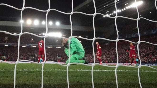 Liverpool's goalkeeper Adrian, bottom, reacts after fails to save the ball as Atletico Madrid's Marcos Llorente scores his side's second goal during a second leg, round of 16, Champions League soccer match between Liverpool and Atletico Madrid at Anfield stadium in Liverpool, England, Wednesday, March 11, 2020.