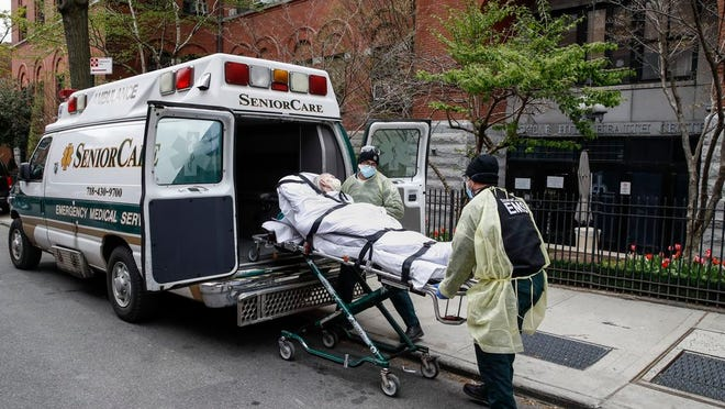 A patient is loaded into the back of an ambulance by emergency medical workers outside Cobble Hill Health Center, Friday, April 17, 2020, in the Brooklyn borough of New York. The despair wrought on nursing homes by the coronavirus was laid bare Friday in a state survey identifying numerous New York facilities where multiple patients have died. Nineteen of the state's nursing homes have each had at least 20 deaths linked to the pandemic. Cobble Hill Health Center was listed as having 55 deaths.