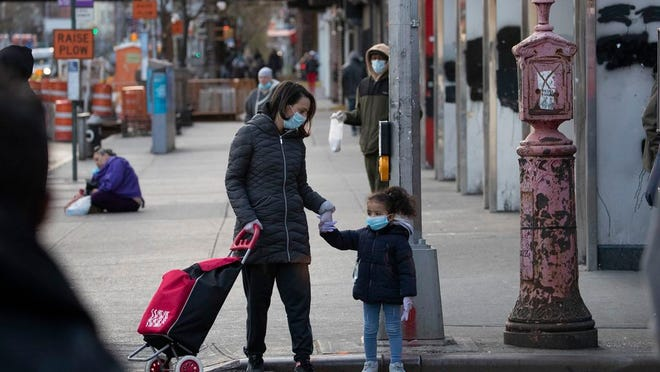 A mother and daughter wearing face masks wait to cross a street in the Harlem section of New York, Thursday, April 16, 2020. Gov. Andrew Cuomo extended stay-at-home restrictions Thursday through mid-May due to the coronavirus.