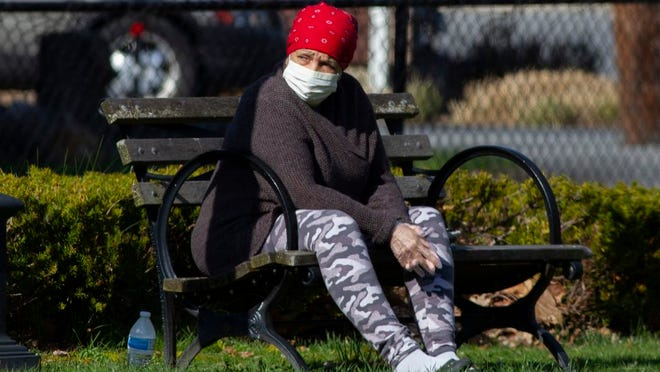 A woman enjoys some warm sun while sitting on a park bench at Railroad Green in Warwick on Sunday April 12, 2020 ROBERT G BREESE