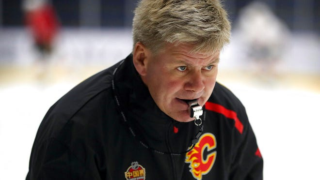 From Sept. 17, 2018, Calgary Flames head coach Bill Peters watches his team practice in Beijing, China. Peters made a return to professional hockey on Wednesday, April 15, 2020, when he was appointed coach of Russian hockey club Avtomobilist Yekaterinburg. Peters resigned as coach of the Calgary Flames last year following allegations he previously used racial slurs and struck players.