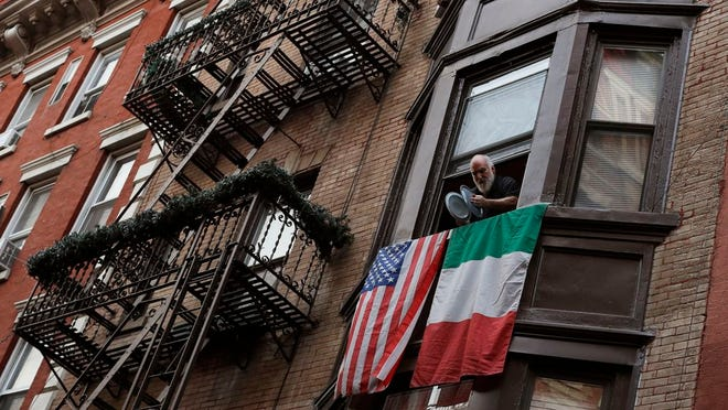 A man leans out the window on Mulberry Street in New York's Little Italy and bangs together pot lids to show his support for those in the front lines fighting against the coronavirus pandemic, Monday, April 13, 2020. Citywide people open their windows each evening at 7 p.m. to make noise to support the doctors, nurses, hospital staff, EMT's and front-line workers who are risking their lives every day.