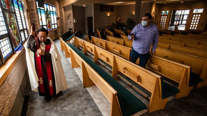 Knight of Columbus member Michael Martin, right, uses Facebook to livestream Assistant Father Anthony Trung as he walks the stations during a Stations of the Cross Mass at Our Lady of Mount Carmel church in Middletown on Friday, April 10, 2020.