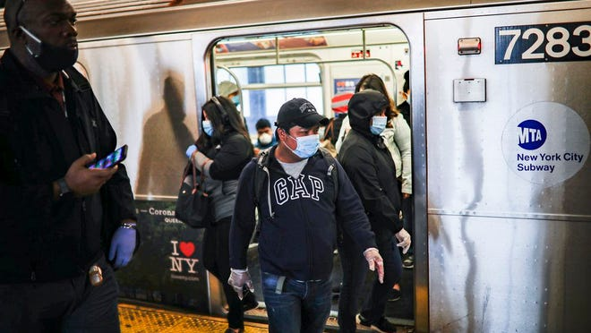 Subway riders, wearing personal protective equipment due to COVID-19 concerns, step off a train, Tuesday, April 7, 2020, in New York. The new coronavirus causes mild or moderate symptoms for most people, but for some, especially older adults and people with existing health problems, it can cause more severe illness or death.