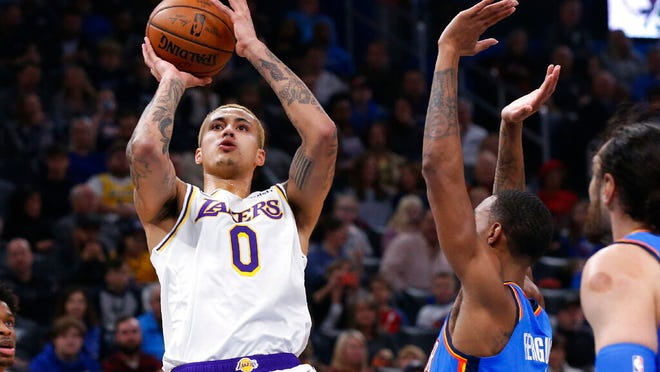 Los Angeles Lakers forward Kyle Kuzma (0) shoots in front of Oklahoma City Thunder guard Terrance Ferguson, center, in the first half of an NBA basketball game Saturday, Jan. 11, 2020, in Oklahoma City.
