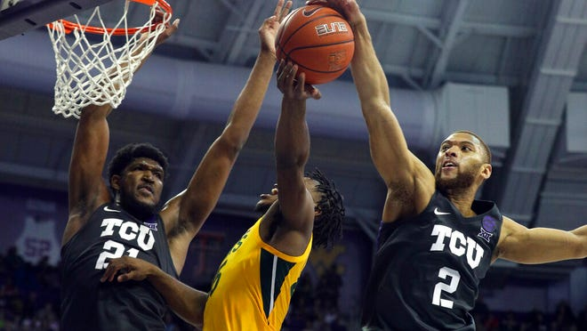 TCU center Kevin Samuel (21) and guard Edric Dennis (2) defend against a shot by Baylor guard Davion Mitchell (45) during the second half of an NCAA college basketball game on Saturday, Feb. 29, 2020 in Fort Worth, Texas.