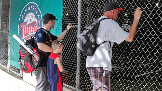 Baseball fans look through a fence at Hammond Stadium after a game between the Minnesota Twins and the Baltimore Orioles was canceled Thursday, March 12, 2020, in Fort Myers, Fla. Major League Baseball has suspended the rest of its spring training game schedule because of the coronavirus outbreak. MLB is also delaying the start of its regular season by at least two weeks.