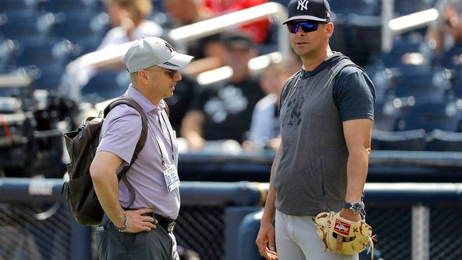 Brian Cashman, left, general manager of the New York Yankees, talks with manager Aaron Boone prior to a spring training baseball game against the Washington Nationals, Thursday, March 12, 2020, in West Palm Beach, Fla.