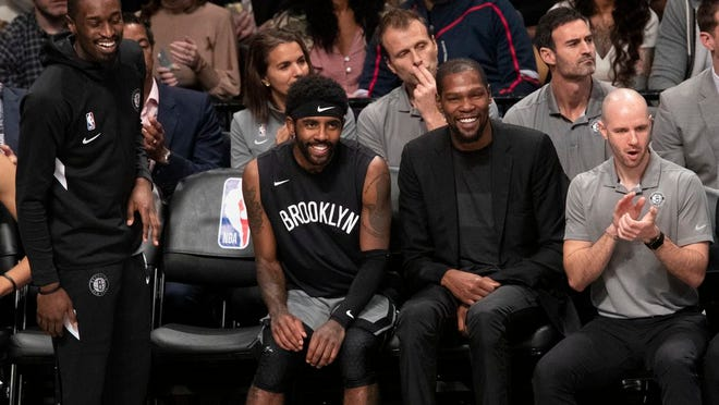 Brooklyn Nets guard Theo Pinson, left, guard Kyrie Irving, center and forward Kevin Durant watch the game action during the second half of an NBA basketball game against the Houston Rockets, Friday, Nov. 1, 2019, in New York. The Nets won 123-116.