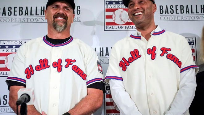 From Jan. 22, 2020, former New York Yankees shortstop Derek Jeter, right, and former Colorado Rockies outfielder Larry Walker pose after receiving their Baseball Hall of Fame jerseys during a baseball news conference in New York.  Jeter and Walker and the rest of this year's Baseball Hall of Fame class will have to wait for their big moment at Cooperstown. The Hall of Fame announced Wednesday, April 29, 2020, that it has canceled its July 26 induction ceremony because of the coronavirus outbreak.