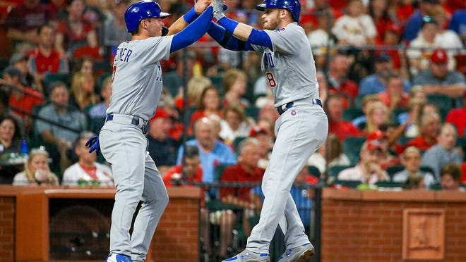 """From Sept. 28, 2019, Chicago Cubs' Nico Hoerner, left, celebrates with teammate Ian Happ after Happ hit a two-run home run during the third inning of a baseball game against the St. Louis Cardinals in St. Louis. When the coronavirus pandemic stopped spring training last month, Ian Happ offered Nico Hoerner, Zack Short and Dakota Mekkes a place to stay if they wanted to remain in Arizona. That's how """"The Compound"""" was born."""