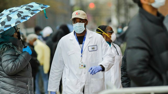 A medical worker walks past people lined up Thursday at Gotham Health East New York, a COVID-19 testing center in Brooklyn.
