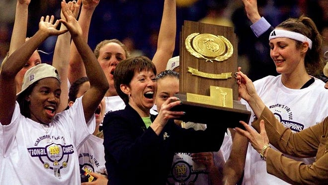 From April 1, 2001, Notre Dame coach Muffet McGraw, center, holds up the National Championship trophy after Notre Dame defeated Purdue 68-66 for the 2001 Women's Final Four Championship in St. Louis. At left is Imani Dunbar and Ruth Riley is at right. McGraw abruptly retired Wednesday, April 22, 2020, stepping down from Notre Dame after a Hall of Fame coaching career that includes two national championships in 33 seasons.