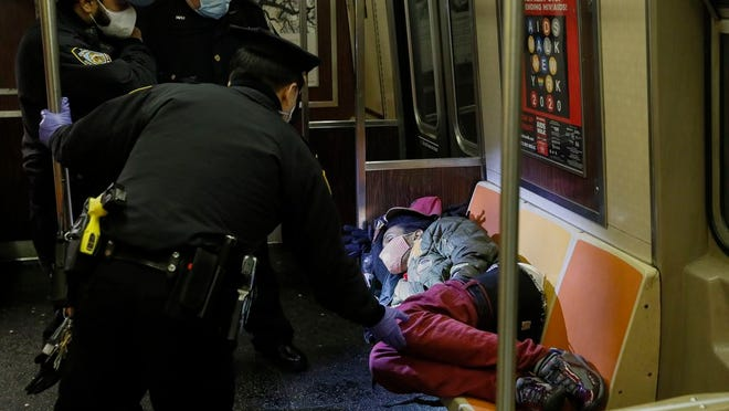 NYPD and MTA officers wake up a sleeping passenger before directing him to exit the 207th Street A-train station, Thursday, April 30, 2020, in the Manhattan borough of New York.