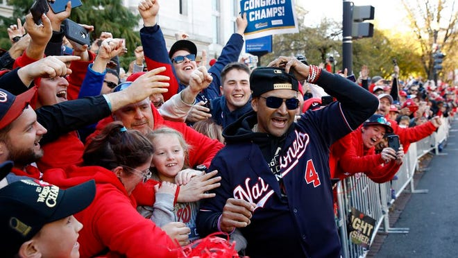 From Nov. 2, 2019, Washington Nationals manager Dave Martinez celebrates with fans during a parade to celebrate the team's World Series baseball championship over the Houston Astros in Washington. Martinez says the World Series champs will raise their banner and present their rings at their stadium with fans in attendance -- no matter how or when or if the 2020 season starts. Like his general manager, Mike Rizzo, Martinez is optimistic there will be a major league season this year and has been mapping out what a second spring training camp might look like.
