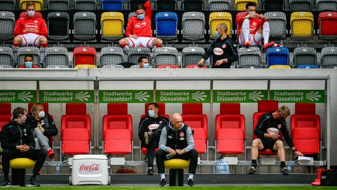 Fortuna Duesseldorf's German head coach Uwe Roesler sits on the sideline during the Bundesliga soccer match between Duesseldorf and  Paderborn in the Merkur Spiel-Arena, Duesseldorf, Germany, Saturday, May 16, 2020. The German Bundesliga becomes the world's first major soccer league to resume after a two-month suspension because of the coronavirus pandemic.