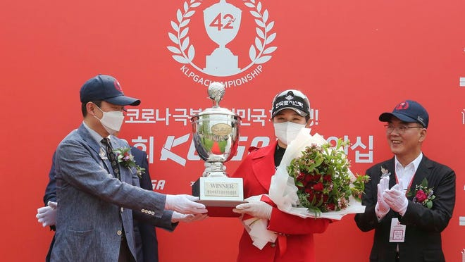 Park Hyun-kyung wearing a face mask of South Korea holds the trophy after winning the KLPGA Championship at the Lakewood Country Club in Yangju, South Korea, Sunday, May 17, 2020.