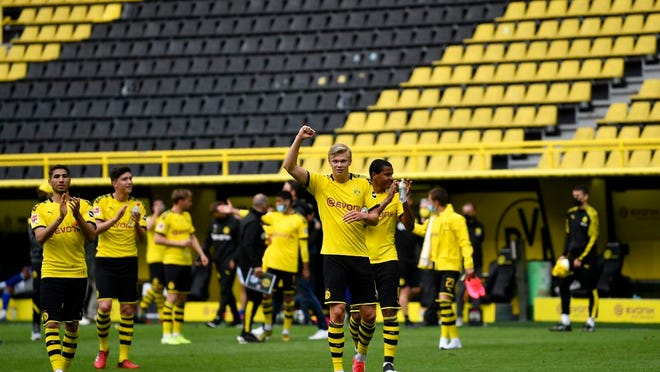 Dortmund's Erling Haaland, center, and his teammates celebrate at the end of the German Bundesliga soccer match between Borussia Dortmund and Schalke 04 in Dortmund, Germany, Saturday, May 16, 2020. The German Bundesliga becomes the world's first major soccer league to resume after a two-month suspension because of the coronavirus pandemic. Dortmund won 4-0.
