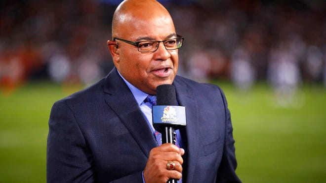 From Sept. 5, 2019, NBC sportscaster Mike Tirico works the sidelines during an NFL football game between the Green Bay Packers and the Chicago Bears in Chicago. Tirico is one of many announcers who has had to trade the press box for a home office.