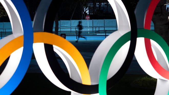 From March 30, 2020, a man jogs past the Olympic rings in Tokyo. Almost two months after the Tokyo Olympics were postponed until next year, CEO Toshiro Muto on Friday, May 15, 2020, said he still could not give an estimate of how much the delay will cost.