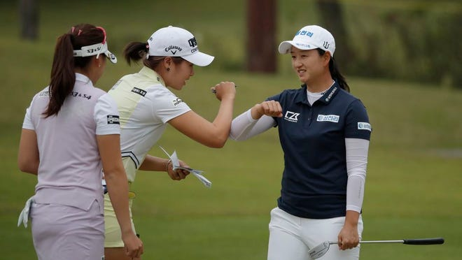 Lee Jeong-eun of South Korea, second from left, reacts with Park Chae-yoon, right, on the 18th hole after finishing the first round of the 42nd KLPGA Championship golf at the Lakewood Country Club in Yangju, South Korea, Thursday, May 14, 2020.