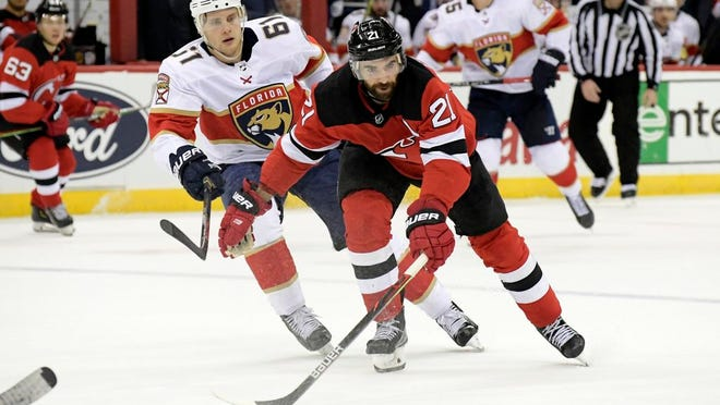 From Feb. 11, 2020, New Jersey Devils right wing Kyle Palmieri (21) and Florida Panthers defenseman Riley Stillman (61) chase after the puck during the second period of an NHL hockey game in Newark, N.J. Palmieri remembers March 12, 2020, like it was yesterday. The Devils came to the Prudential Center in Newark, N.J., that morning for a pregame skate before playing the Carolina Hurricanes at home that night. They never skated. The rumors that the NHL was going to pause the season were circulating and it was not long before the league put the season on hold because of the coronavirus pandemic.