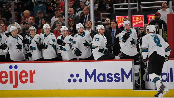 From March 11, 2020, San Jose Sharks' Evander Kane (9) celebrates with teammates on the bench after scoring a goal during the first period of an NHL hockey game against the Chicago Blackhawks in Chicago. The Sharks had started planning for next season long before the news became official that they would be one of the seven teams left home if the NHL resumes its season.