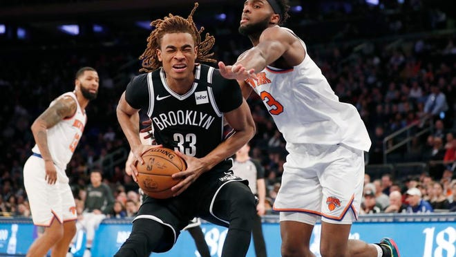 New York Knicks center Mitchell Robinson (23) defends Brooklyn Nets forward Nicolas Claxton (33) during the second half of an NBA game in New York, Sunday, Jan. 26, 2020. The Nets are likely to resume play this season, but the Knicks may not.