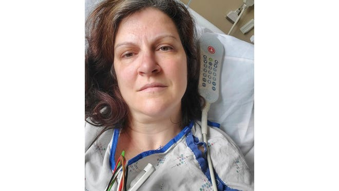 """This May 6, 2020 photo provided by Darlene Gildersleeve, 43, of Hopkinton, N.H. shows her at a Manchester, N.H. hospital. Gildersleeve thought she had recovered from COVID-19. Doctors said she just needed rest. And for several days, no one suspected her worsening symptoms were related — until a May 4 video call, when her physician heard her slurred speech and consulted a specialist. """"You've had two strokes,'' a neurologist told her at the hospital."""