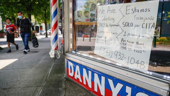 Pedestrians pass a barbershop that displays a sign advertising haircuts by appointment only, Tuesday, May 26, 2020, in New Rochelle, N.Y.