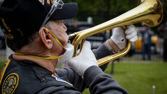 A bugler plays Taps as a motorcade of veterans stops outside the VA Medical Center for a wreath laying ceremony beside memorial stones on the premises, Monday, May 25, 2020, in the Brooklyn borough of New York.