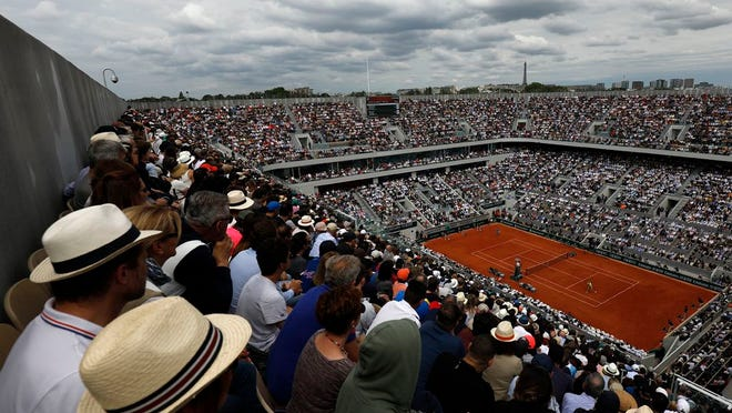 From June 9, 2019, spectators watch Austria's Dominic Thiem playing Spain's Rafael Nadal, right, on center court during the men's final match of the French Open tennis tournament at the Roland Garros stadium in Paris. It should have been the first day of the French Open tennis tournament, with thousands of fans flocking to Roland Garros in western Paris hoping to catch a glimpse of 12-time champion Rafael Nadal or No. 1 Novak Djokovic. Instead, the grounds are deserted amid the coronavirus pandemic, with the famed tennis tournament on hold until late September.