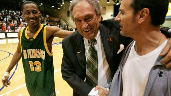 From Feb. 2, 2008, San Francisco head coach Eddie Sutton shakes the hand of Terry Anzaldo as Myron Strong, left, smiles after San Francisco defeats Pepperdine 88-85 in an NCAA college basketball game to give Sutton his 800th win, in Malibu, Calif. Sutton, the Hall of Fame basketball coach who led three teams to the Final Four and was the first coach to take four schools to the NCAA Tournament, died Saturday, May 23, 2020. He was 84.
