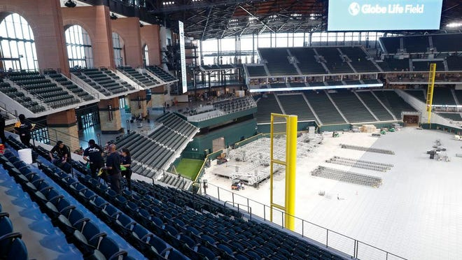 From March 11, 2020. workers clean seats inside the newly constructed Globe Life Field in Arlington Texas. The Texas Rangers would prefer to stay home in their new ballpark whenever it is time to get back to spring training. They still haven't played a game, or even had an organized workout, in their $1.2 billion stadium with a retractable roof. General manager Jon Daniels says, Tuesday , May 19, 2020, there would be a lot of advantages to workouts in Texas instead of returning to their camp Arizona. Spring training has been on hold more than two months ago because of the coronavirus pandemic.