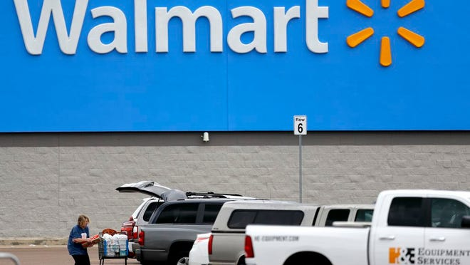 FILE - In this March 31, 2020 file photo, a woman pulls groceries from a cart to her vehicle outside of a Walmart store in Pearl, Miss.  Walmart became a lifeline to millions of people as the coronavirus spread, and its profit and sales surged during the first quarter, topping almost all expectations.