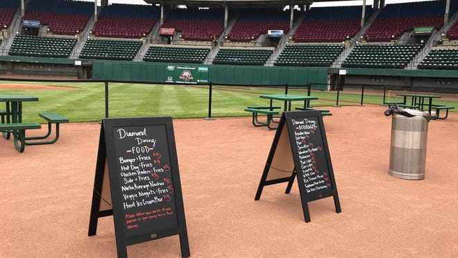 """Menu boards and tables occupy the third base infield dirt in preparation for dining guests at McCoy Stadium, home of the Pawtucket Red Sox, in Pawtucket, Rhode Island, Wednesday, May 27, 2020. With the minor league baseball season on hold due to the coronavirus pandemic, the Triple-A affiliate of the Boston Red Sox had found another use for its home field. Starting next weekend, """"Dining on the Diamond"""" will allow PawSox fans and others just longing for a taste of baseball to sample typical ballpark fare on the McCoy Stadium infield."""