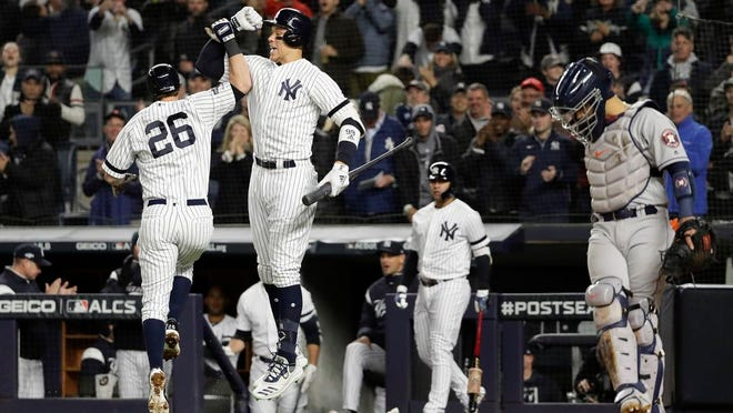 New York Yankees DJ LeMahieu (26) celebrates with Aaron Judge after hitting a solo home run against the Houston Astros during the first inning of Game 5 of baseball's American League Championship Series, Friday, Oct. 18, 2019, in New York.