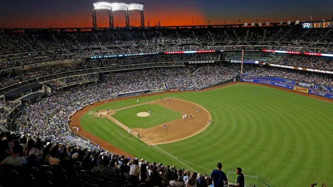 From Aug. 29, 2019, the sun sets behind Citi Field during a baseball game between the New York Mets and the Chicago Cubs in New York. Major League Baseball players ignored claims by clubs that they need to take additional pay cuts, instead proposing they receive a far higher percentage of salaries and a commit to a longer schedule as part of a counteroffer to start the coronavirus-delayed season.