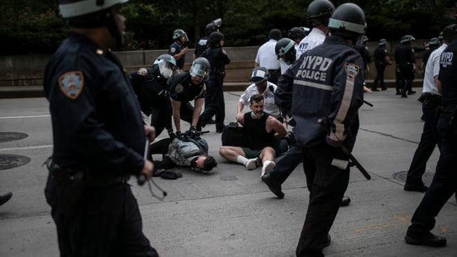 Police arrest protesters refusing to get off the streets during an imposed curfew while marching in a solidarity rally calling for justice regarding the death of George Floyd, Tuesday, June 2, 2020, in New York. Floyd died after being restrained by Minneapolis police officers on May 25.
